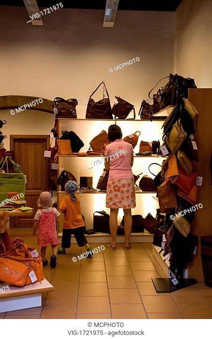 woman and children in bag shop - Toskana; Toscana, Italien, 31/05/2008