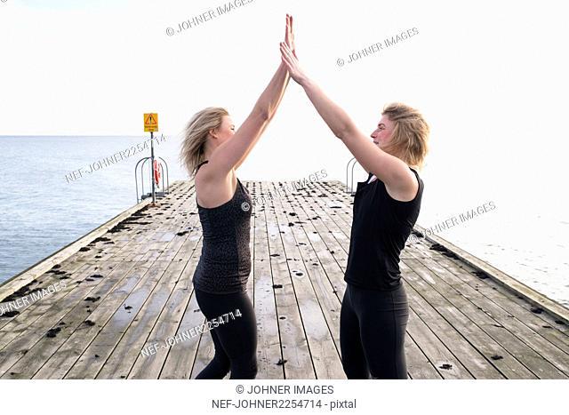 Women giving high-five on pier
