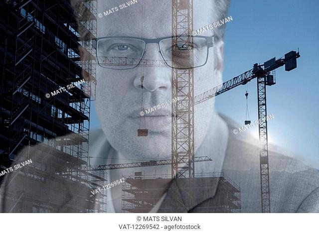 Portrait of a businessman with construction of a building and crane; Locarno, Ticino, Switzerland