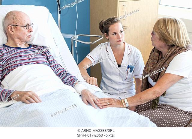 MODEL RELEASED. Woman visiting senior man in hospital talking to nurse