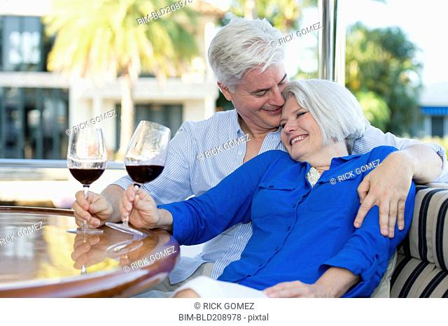 Older Caucasian couple having wine together on boat