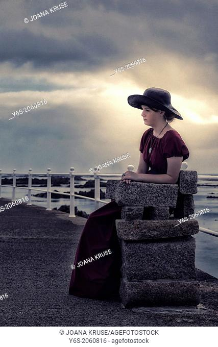 a sad girl with a black sunhat sitting on a stone bench at the sea