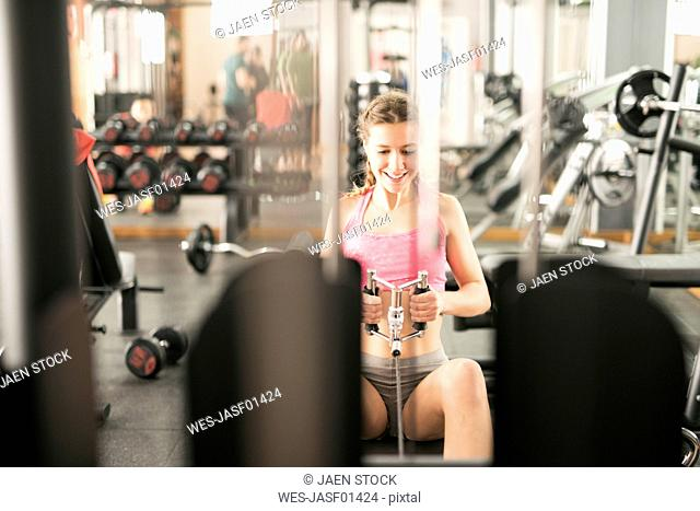 Woman training in gym with rowing machine