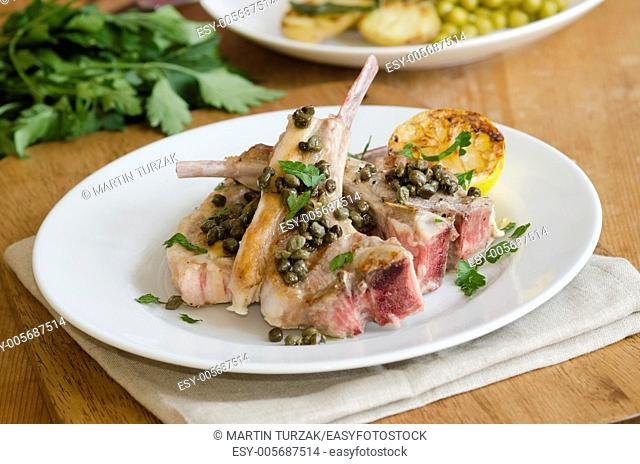 Grilled lamb chops with anchovies and capers on a plate