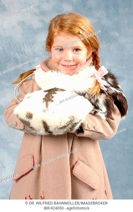 Little girl wearing a winter coat and a muff