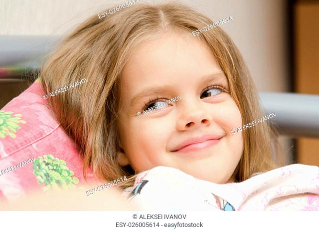 Cheerful five year old girl lying on the bed and looked left smorit