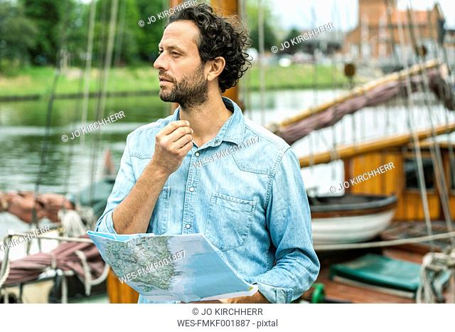 Germany, Luebeck, man at landing stage holding map