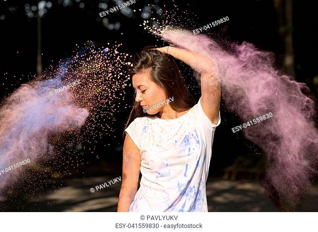 Adorable brunette asian woman in white t shirt celebrating Holi Festival