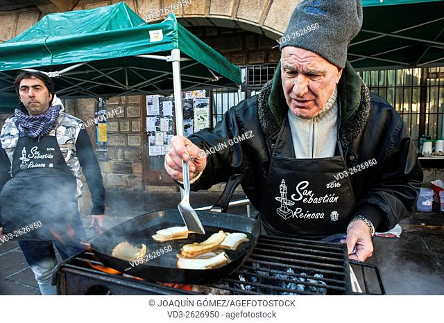 "A participant in the feast of San Sebastian in Reinosa (Cantabria) prepares a """"bacon"""" in the coals is typical make food through the streets of the town"