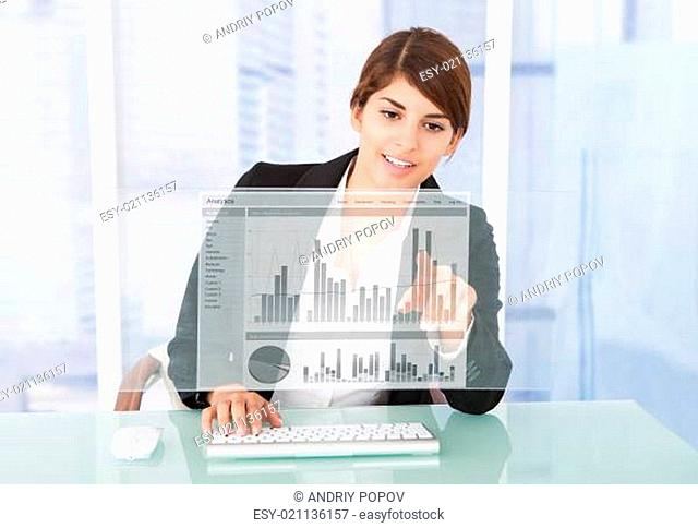 Happy Businesswoman Working On Graph At Computer Desk