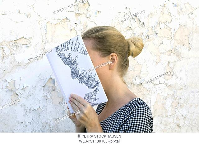 Woman covering face with book, reading poetry in front of wall