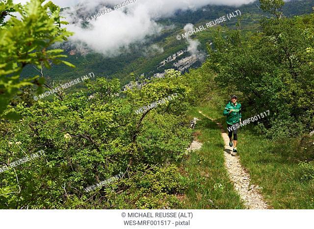 Italy, Trentino, man running near Lake Garda