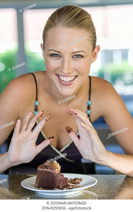 Young blond woman enjoying chocolate cake