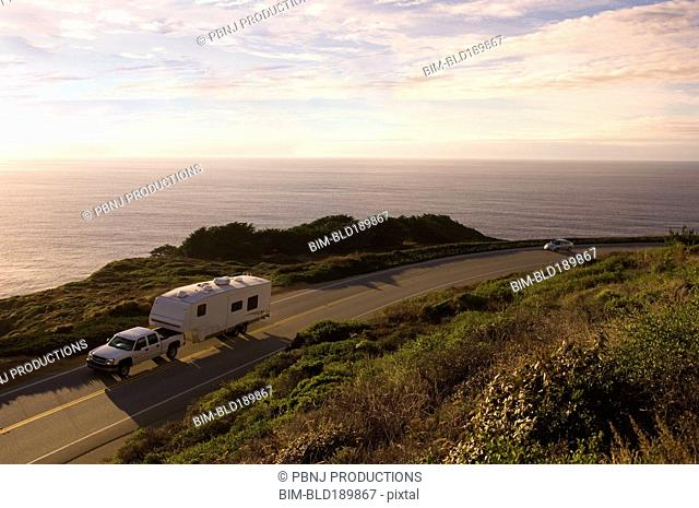 Truck pulling camper on coastal highway