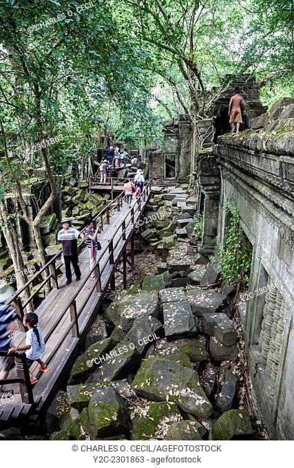 Cambodia, Beng Mealea, 12th. Century. Tourists on Walkway through Sanctuary Ruins