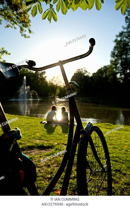 Couple relaxing beside lake in the Vondelpark in the evening; Amsterdam, Holland