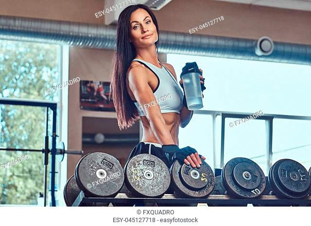 Beautiful sexy athletic brunette female in a sportswear, standing with a bottle of a water near a counter with dumbbells