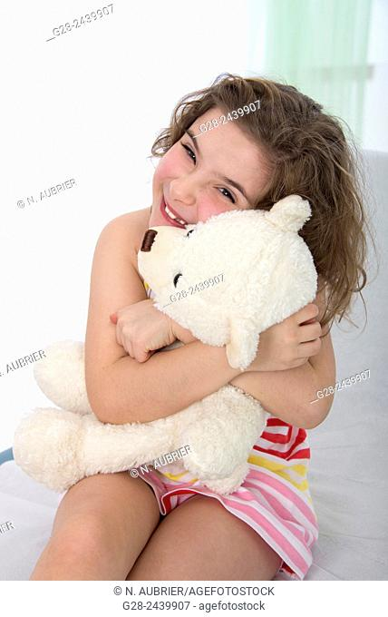 Smiling and laughing little girl cuddling her teddy bear