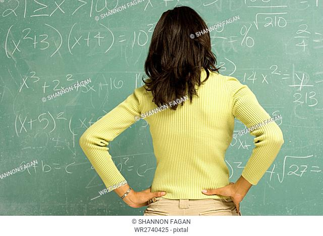 Female student stood in front of blackboard