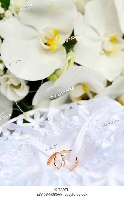 white orchids and wedding rings on bridal pillow