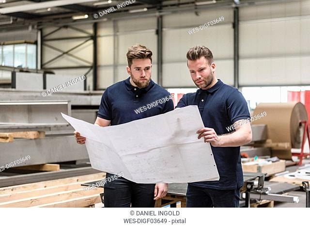 Two men looking at plan in factory