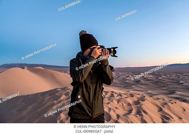 Man taking photograph, Khongor sand dunes, Gobi desert, Mongolia