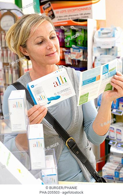 Woman buying Alli medicine in pharmacy. Alli is a half-dose version of the diet drug Xenical Orlistat produced by GlaxoSmithKline GSK
