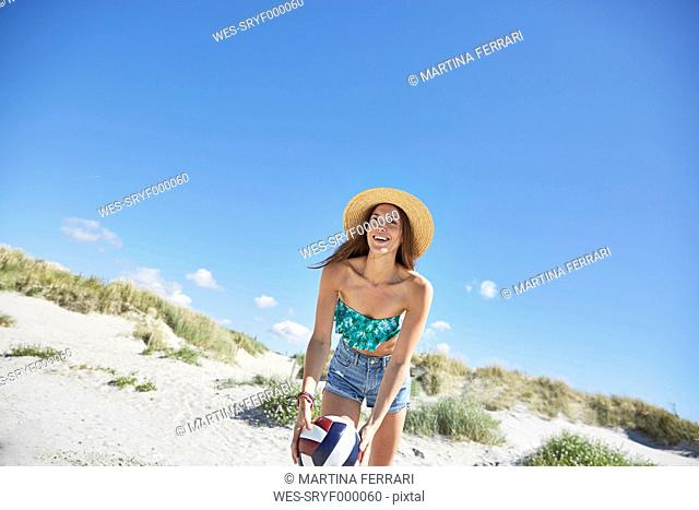 Young woman on the beach playing beach volleyball