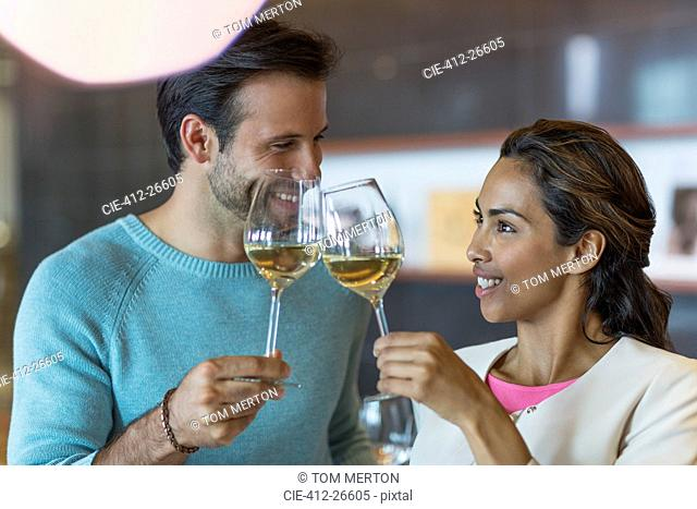 Smiling couple toasting white wine glasses
