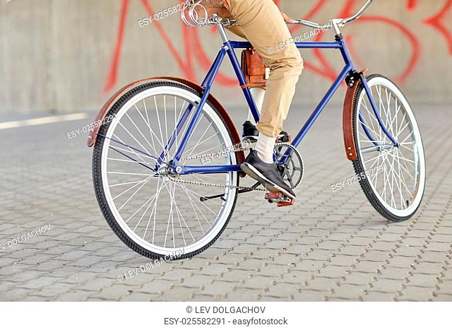 people, style and lifestyle - close up of hipster man riding fixed gear bike on city street