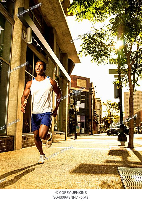 Young man running on city street