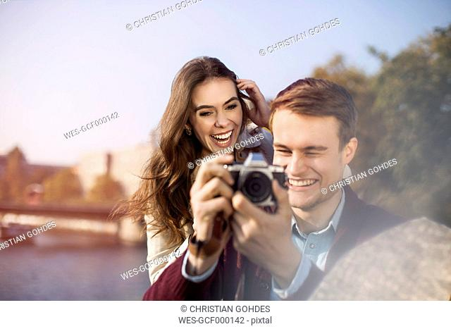 Germany, Berlin, happy young couple with camera at bank of River Spree