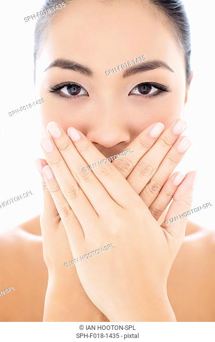MODEL RELEASED. Young Asian woman with hands touching covering mouth, portrait