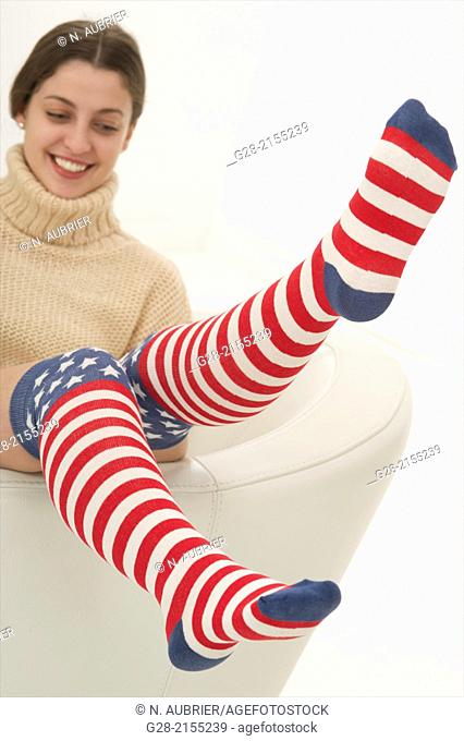 young beautiful happy woman, bouncing upon a white leather armchair, with funny stars and stripes knee high socks