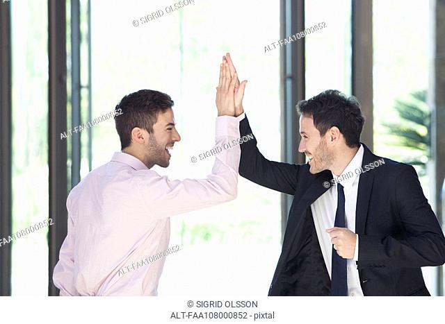 Businessmen congratulating each other with high-five