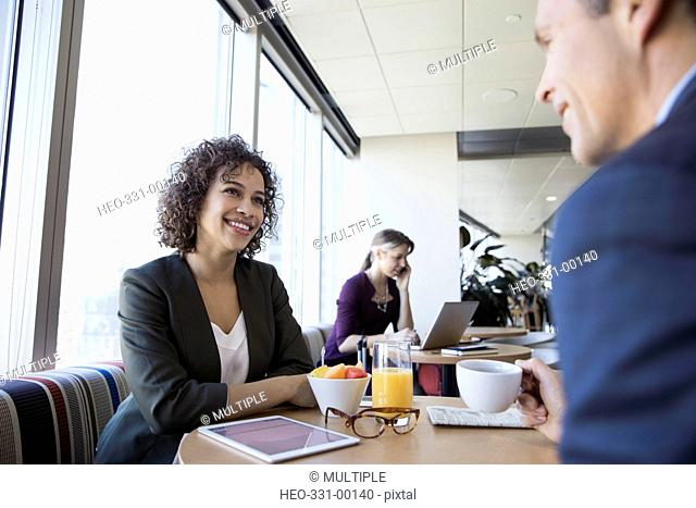 Businessman and businesswoman talking, drinking coffee at airport breakfast lounge