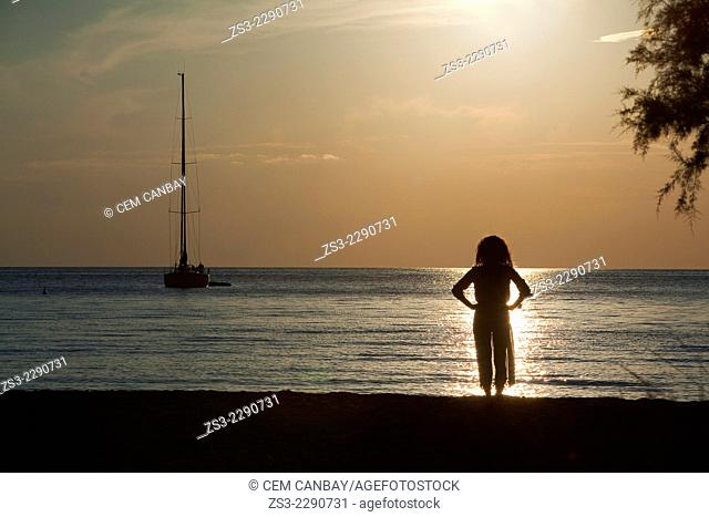 Silhouette of a woman standing on the beach near the port in Kamares at sunset, Sifnos, Cyclades Islands, Greek Islands, Greece, Europe