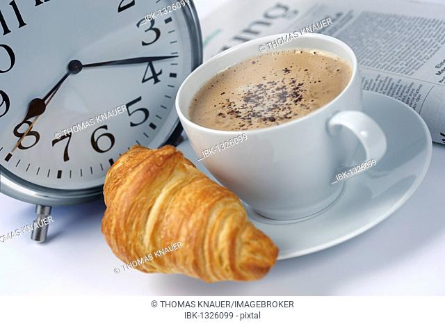 Croissants, coffee, alarm clock, newspaper, symbolic image for a quick breakfast