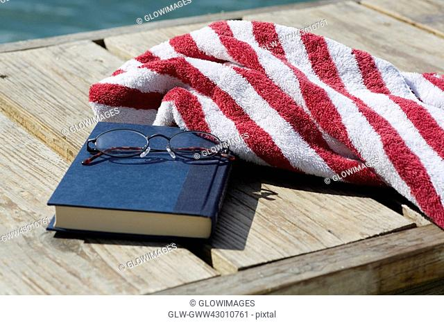 Close-up of a book and a pair of eyeglasses with a towel on a jetty