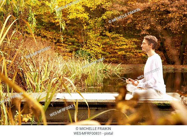 Man practicing yoga on a jetty at a pond in autumn