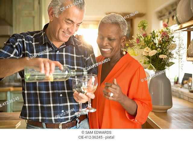 Smiling senior couple pouring white wine in kitchen