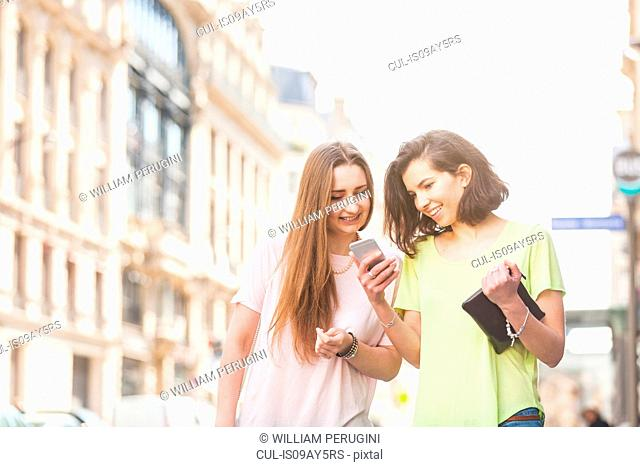 Two young women strolling on street reading smartphone texts, Paris, France