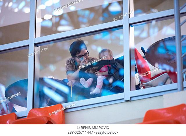 baby child in wheels and mom woman looking trough big modern window panel