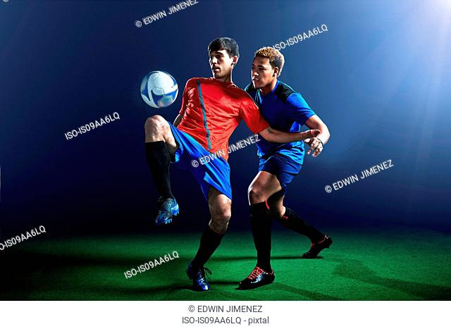 Male soccer players defending ball