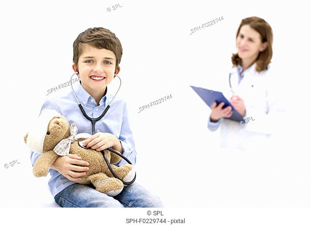 Boy role playing with teddy bear and stethoscope