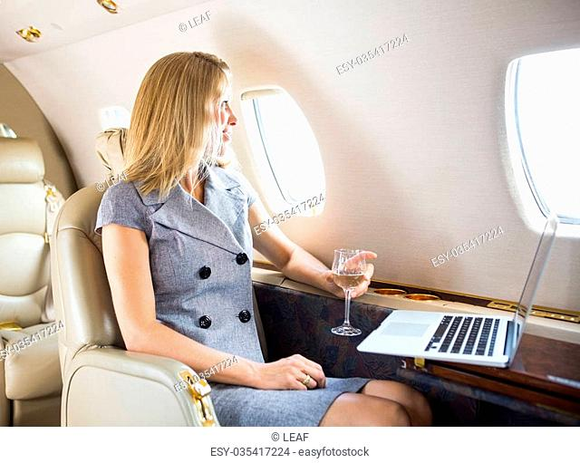 Happy businesswoman holding wineglass while looking through window of private jet