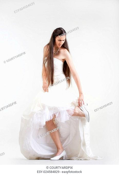 bride in wedding dress taking off her shoe checking her hurting foot