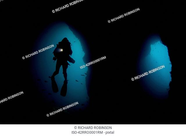 Diver swimming in underwater cave