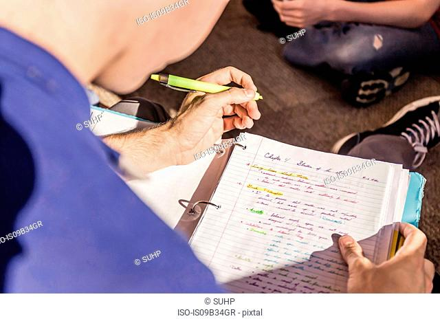 Over shoulder view of teenage boy highlighting notes in high school