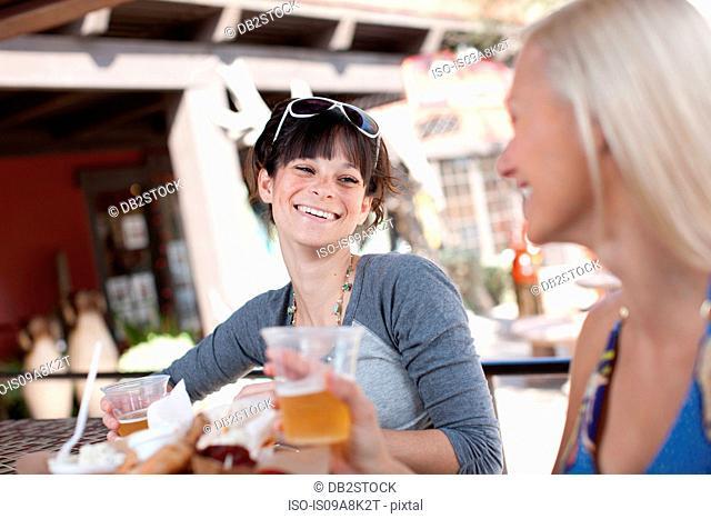 Girlfriends having drinks in outdoor cafe, smiling